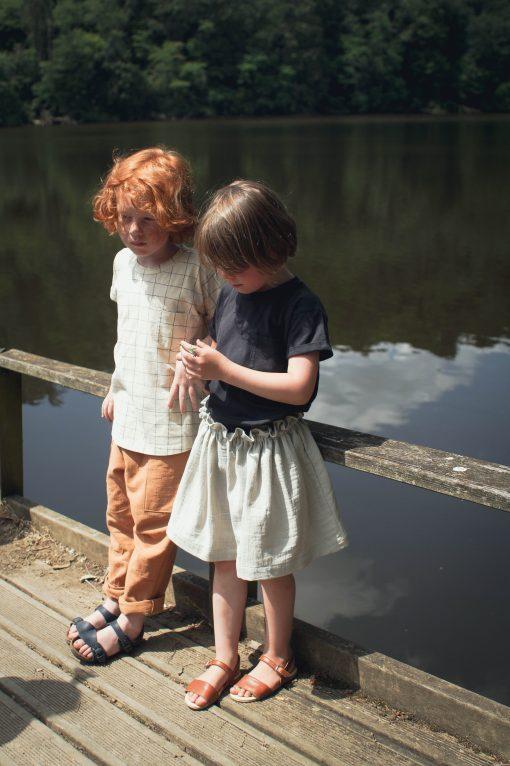 t-shirt enfant Minabulle en jersey de coton bio écru à carreaux et pantalon en crêpe de coton cannelle, t-shirt en jersey de coton bio anthracite et jupe froncée à la ceinture en crêpe de coton gris